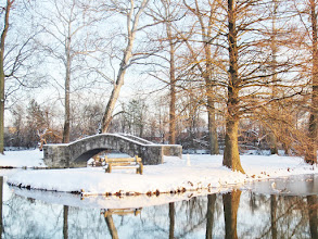 Photo: Stone bridge and bench in the snow by a lake at Eastwood Park in Dayton, Ohio.
