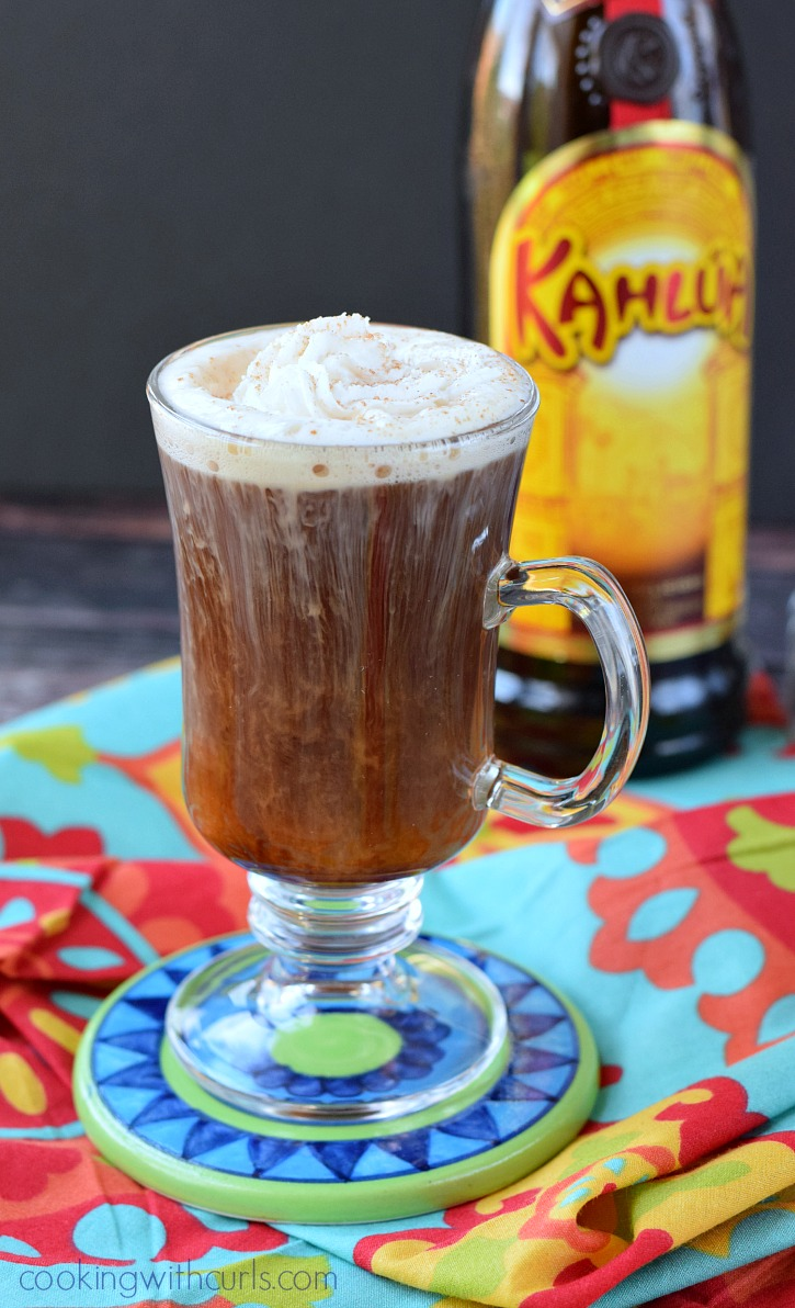 A tequila and Kahlua cocktail in tall, clear, coffee glass; bottle of Kahlua
