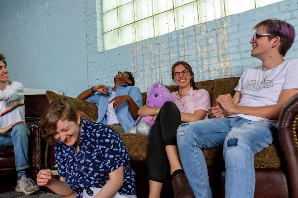 A group of smiling and laughing young people lounge on a sofa together. One of them holds a stuffed purple unicorn. There are twinkly lights hung against the painted brick wall.