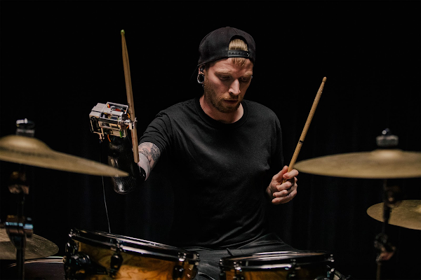 Jason Barnes playing drums against a black backdrop.