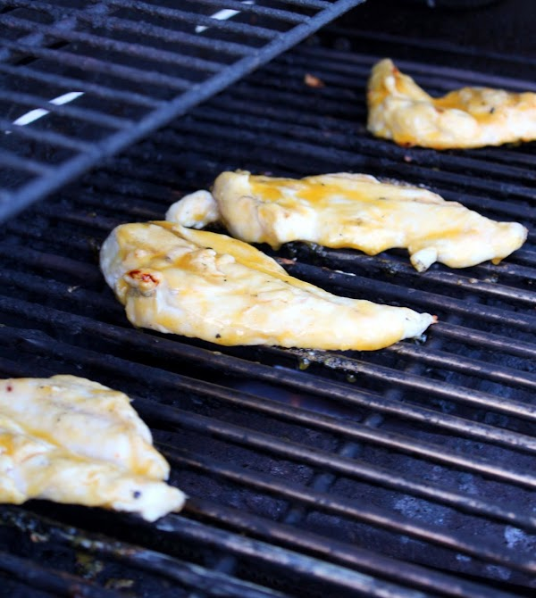 Chicken pieces with sauce on grill.