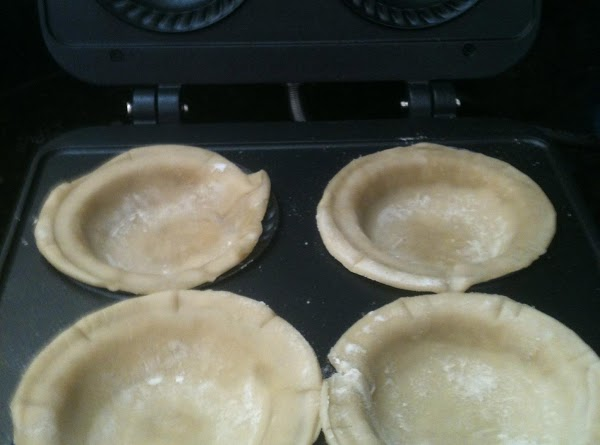 Working quickly, place the pie dough rounds into the pie maker, molding the dough...