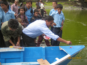 Photo: School teachers inaugurate the boat before sending it off in the water.