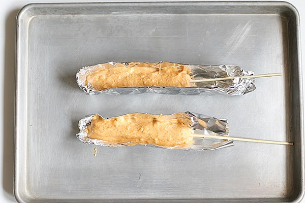 """Put a skewer or Popsicle stick into each hot dog.Prepare the foil """"boats"""" and..."""