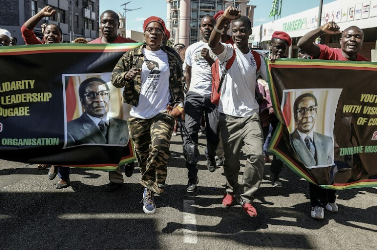 Youth Supporters of Zimbabwean President Robert Mugabe cheer during the Zimbabwe African National Union Patriotic Front One Million Youth March in Harare on Wednesday. Picture: AFP/JEKESAI NJIKIZANA
