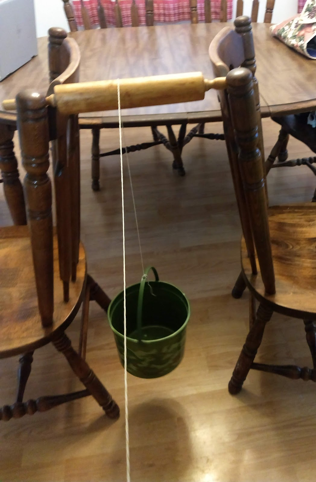 A rolling pin rests on the back of two kitchen chairs with a string draped over, tied to a bucket. The rolling pin is acting as a pulley.