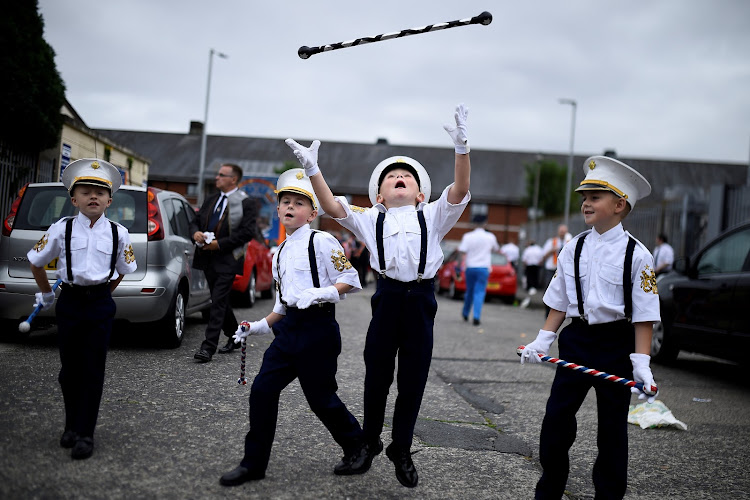 Young members of Loyalist Orders throw a baton in the air as they participate in Twelfth of July celebrations in Belfast, Northern Ireland.