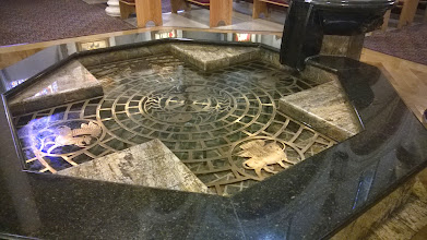 Photo: August 10-I found the baptismal font at St. Francis Basilica to be quite striking with the four Gospel writers.