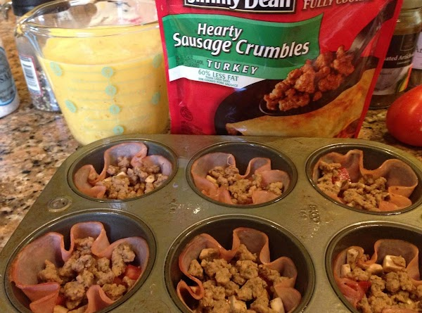 Spray muffin pans with Pam, insert ham slices into muffin pan wells. Spoon 1 TBSP...