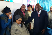 Police minister Bheki Cele comforts the mother of Sgt Donovan Prins, who was gunned down in Lavender Hill, Cape Town, on June 24 2019.