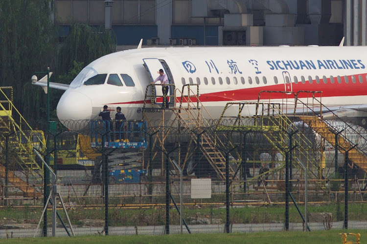 Workers inspect a Sichuan Airlines aircraft that made an emergency landing after a windshield on the cockpit broke off, at an airport in Chengdu, Sichuan province, China May 14, 2018.