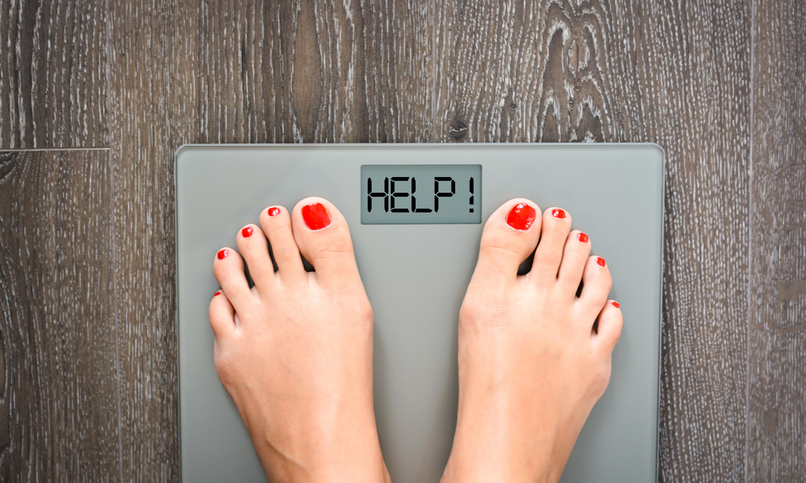 Woman standing on scale that says HELP! for metabolic weight loss