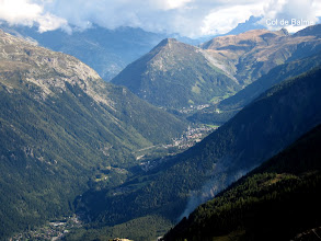 "Photo: From the top we can see the Chamonix valley with the town of Argentiere nestled near the end. The Col de Balme, a pass which separates France from Switzerland, is at the upper right.  Look under the word ""de"" for a barely-visible small white building in the pass--a sort of inn that sits right on the border. We will cross the Col de Balme tomorrow and hike down the other side into Switzerland."