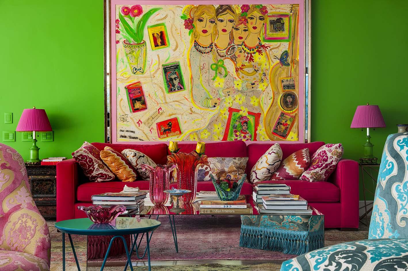 Sofá rosa com almofadas colorida e tapete rosa.