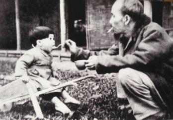 Bác Hồ bón cơm cho cháu bé khi đến thăm một trại nhi đồng ở Việt Bắc, năm 1950.