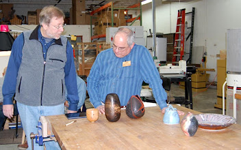 Photo: Show & Tell panelist Steve Keeble shows Mark Verna examples of his wood art collection both virtual on his ipad and physical with those on the table.