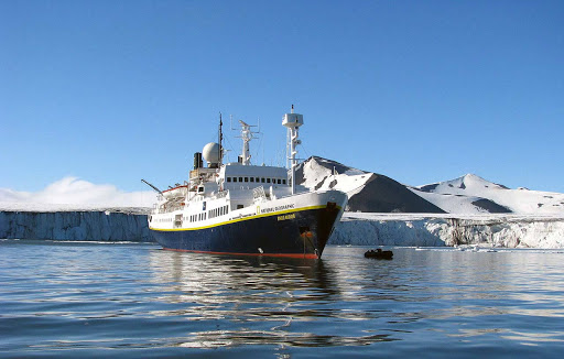 A tiny Zodiac sidles up to National Geographic Endeavor in Svalbard, the rugged region north of mainland Norway.