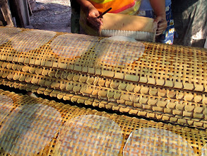 Photo: transferring the thin rice paper onto a woven bamboo rack