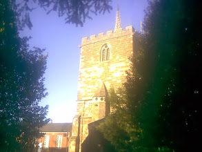 Photo: The church tower captured through the trees in golden winter Sun with the old school house, now a community centre, behind.
