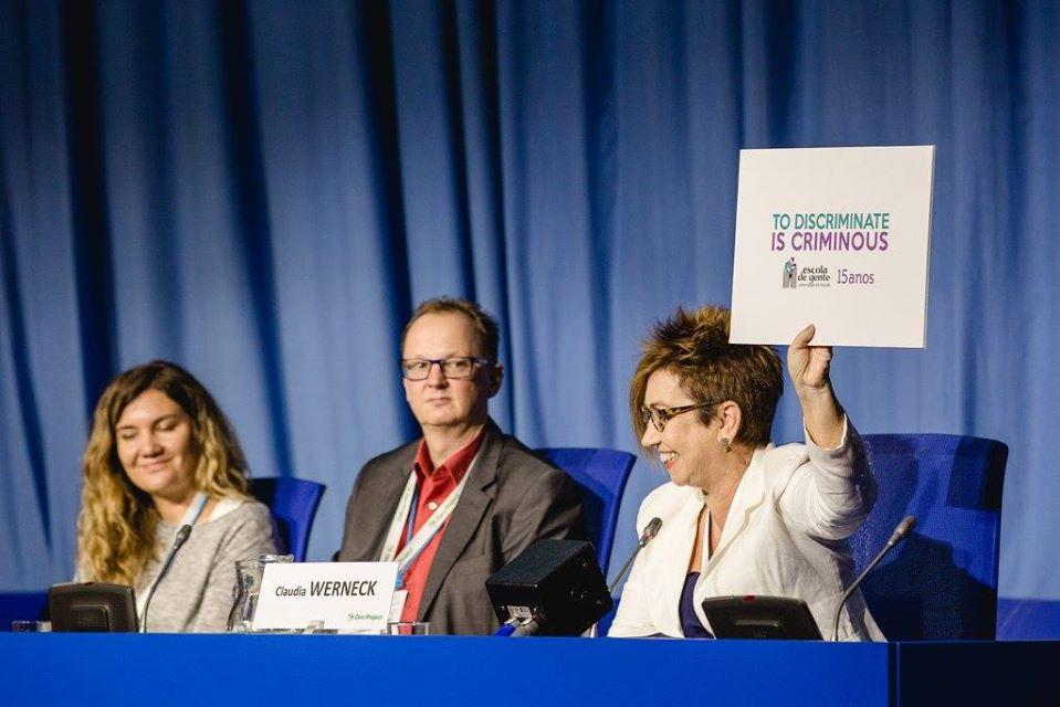 """mulher está sorrindo em uma mesa de debate e levanta placa com o nome da campanha em inglês """"To discriminate is criminous"""". Ao seu lado direito um homem e uma mulher olham para ela. Ao fundo uma cortina azul. A toalha da mesa também é azul."""
