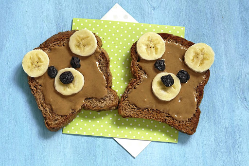 Making bear faces using peanut butter, banana and blueberries.
