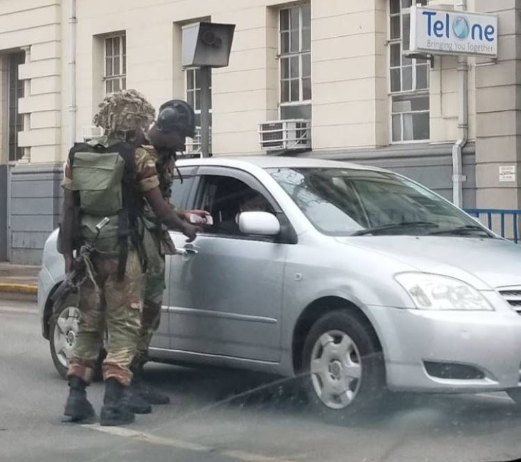Soldiers check identity particulars of civilians right in the heart of Harare city.