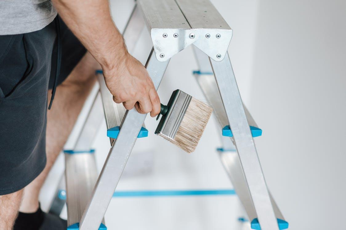 Painter with brush climbing ladder during renovation work