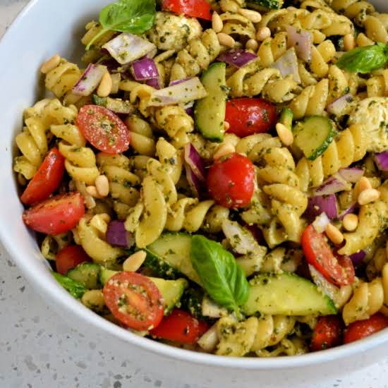 A Delicious Pesto Pasta Salad Made Easy With Fusilli Pasta, Tomatoes, Red Onion, Cucumbers, Mozzarella, And Toasted Pine Nuts.  Use Either Fresh Homemade Pesto Or Store Bought For A Quick And Easy Side Or Light Dinner.