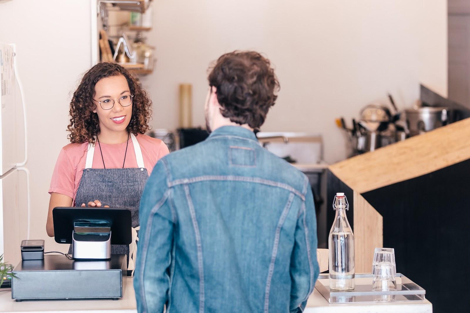 Uma mulher trabalhando no caixa de um estabelecimento e falando com um cliente.