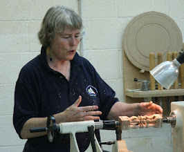 Photo: Barbara shows how to use split turning to produce 4 unique but identical multi-axis spindles while doing all the turning on-axis. Cool!