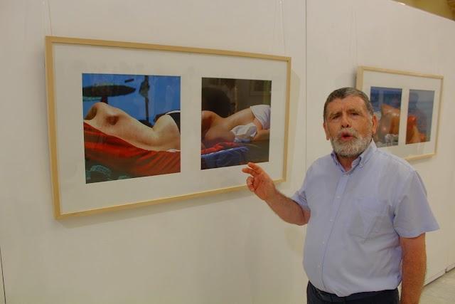 El pintor y grabador Martín Pastor destacando una de las obras expuestas por parejas.
