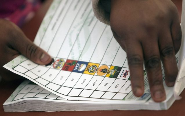 An Election Commission worker tears a ballot paper at a voting station during local municipal elections. Picture: EPA/KEVIN SUTHERLAND
