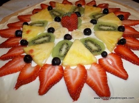 """Now, spread the toppping over the cooled crust.Next, """"decorate"""" with strawberries, bananas, berries, kiwi,..."""