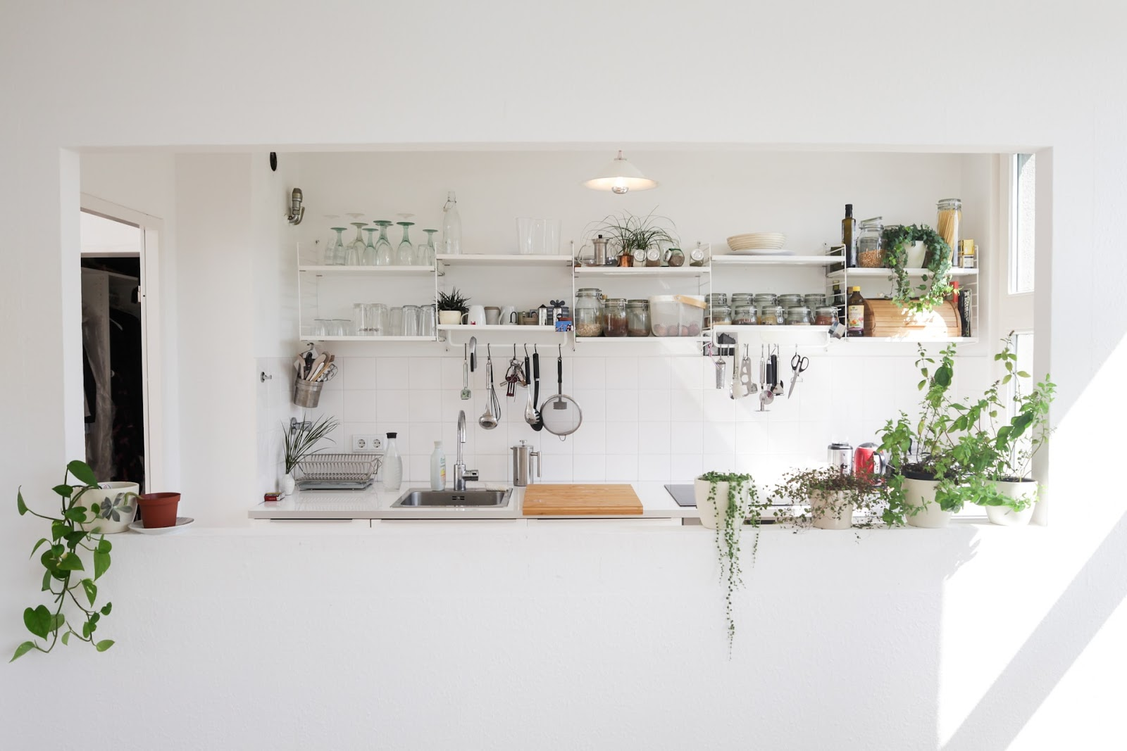 Sunlight streaming into the stark white kitchen from the window on the side making the room appear bright and roomy.