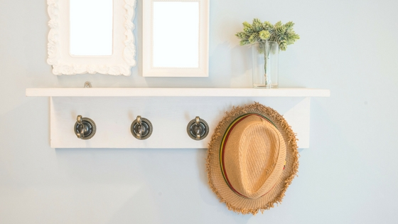Shelf and hooks with a hat hanging on one of the hooks, and small vase of flowers on shelf