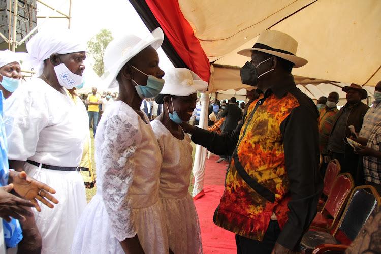 ODM leader Raila Odinga condoles the widows of the late Zachery Origa durin his burial at Ratanga village in Ndhiwa constituency on February 2021