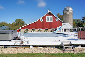 Photo: Clear Spring Farm in rural Welch, MN: Woodstove-heated pool with converted barn behind.