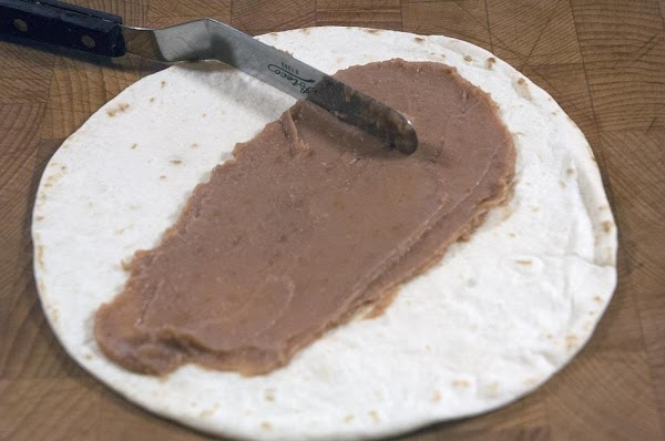 Spread 1 tablespoon of refried beans down the center.