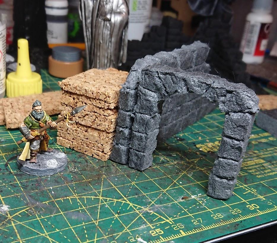 A Frostgrave barbarian next to a partially built terrain piece of a ruin.