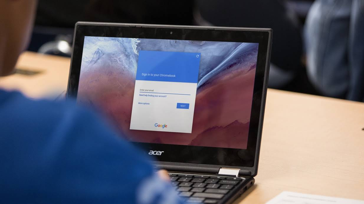 A cropped shot of a student using a Chromebook on a desk, showing the Google log-in screen.