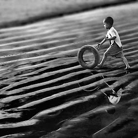 The Baby with the Tyre by Subrata Kar - Babies & Children Children Candids ( sand, pyre, play, baby, beach )