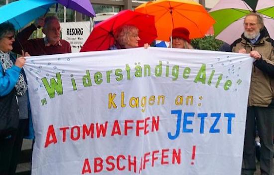 Gruppenbild mit Friedensfreundinnen und Friedensfreunden, aufgepannte Regenschirme, Transparent: «‹Widerständige Alte› klagen an: Atomwaffen jetzt abschaffen!».