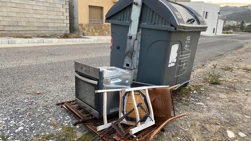Enseres abandonados junto a un contenedor en Olula del Río.