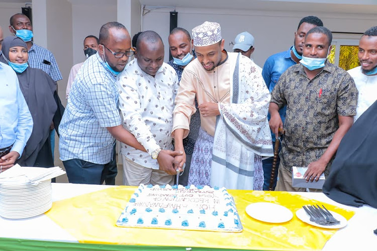 Garissa Education executive Ahmednadhir Omar is joined by his colleagues in cutting a cake when he handed over the health docket on Wednesday, January 13, 2021