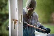 a man in a balaclava breaking a door to break in to a home