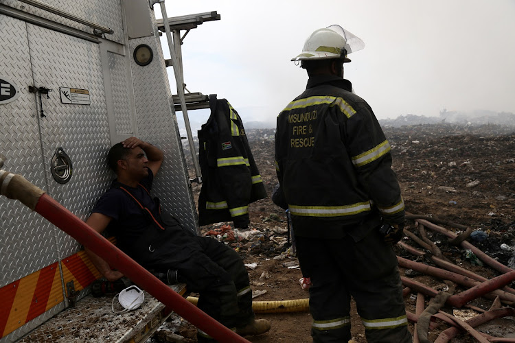 Firefighters rest as they wait for more water at the Msunduzi landfill in Pietermaritzburg.