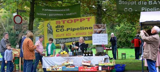 Zahlreiche Menschen protestieren gegen giftiges CO. Im Hintergrund Transparente: »Stoppt die CO-Pipeline…« und »Kohlenmonoxid: farblos, geruchlos, tödlich«. Im Vordergrund: Obst- und Saftstand.