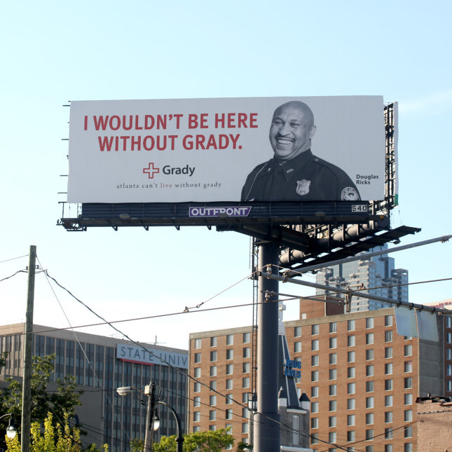 "Billboard by Grady, presenting Douglas Ricks in cop uniform, saying ""I wouldn't be here without Grady."""