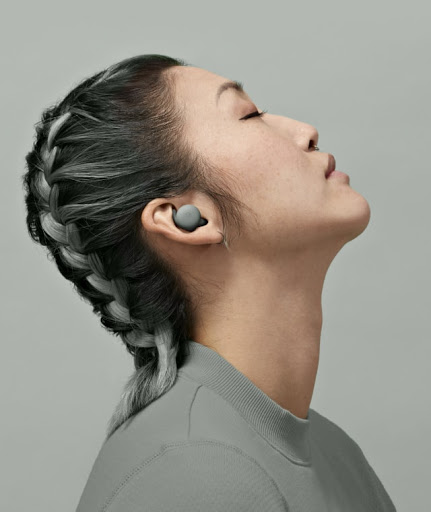 A young woman with her eyes closed and head slightly tilted back is immersed in the audio coming from her Pixel Buds A-Series.