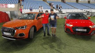 Los dos ganadores con sus coches.